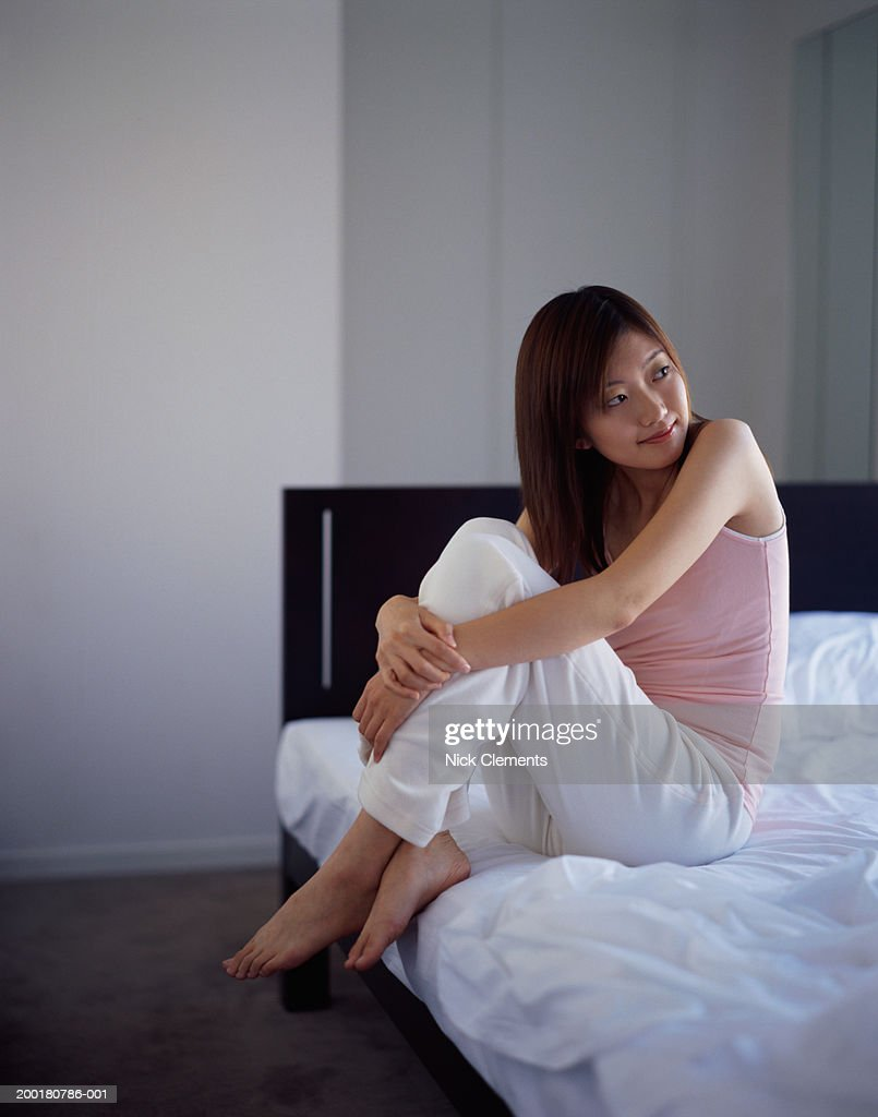 Young woman sitting on bed, smiling : Stock Photo