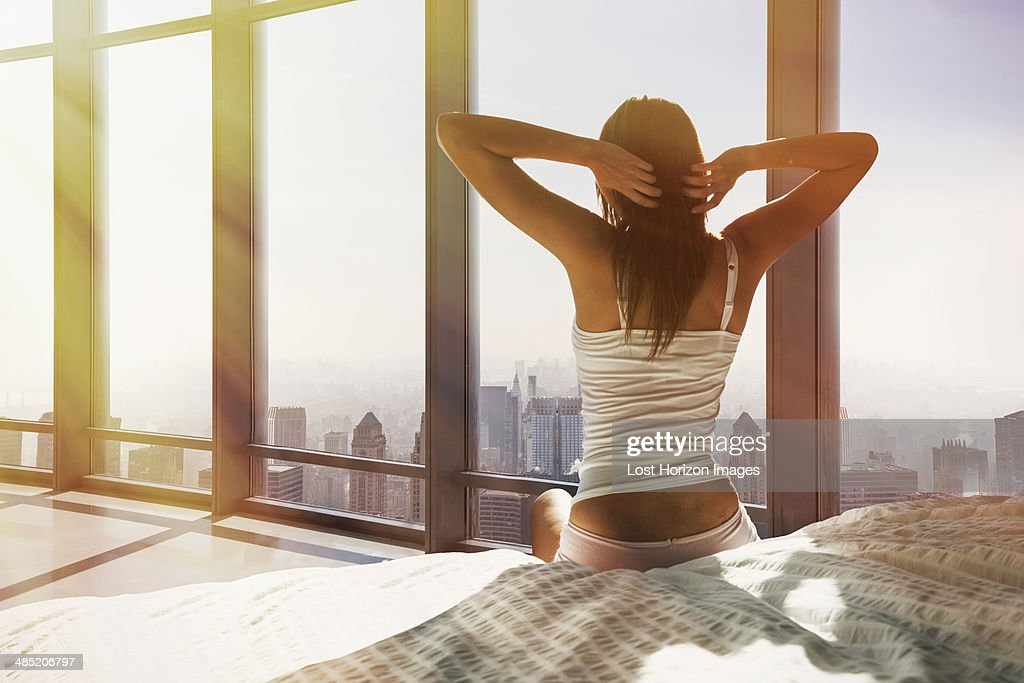 Young woman sitting on bed, stretching, overlooking city : Stock Photo