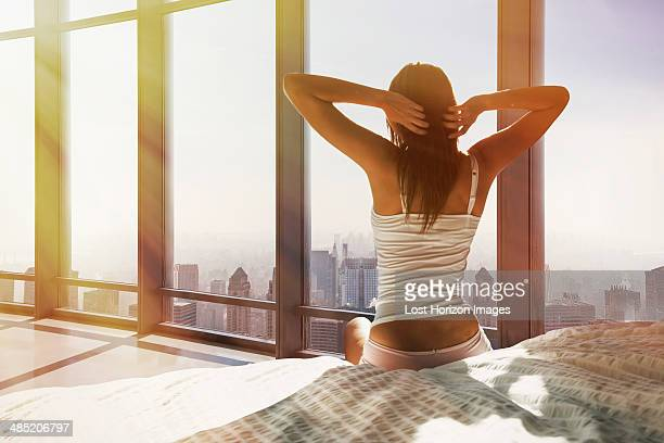 Young woman sitting on bed, stretching, overlooking city