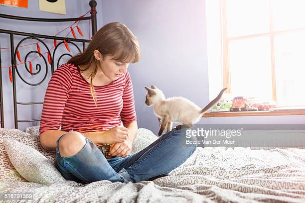 Young woman sitting on bed with kitten on knee.