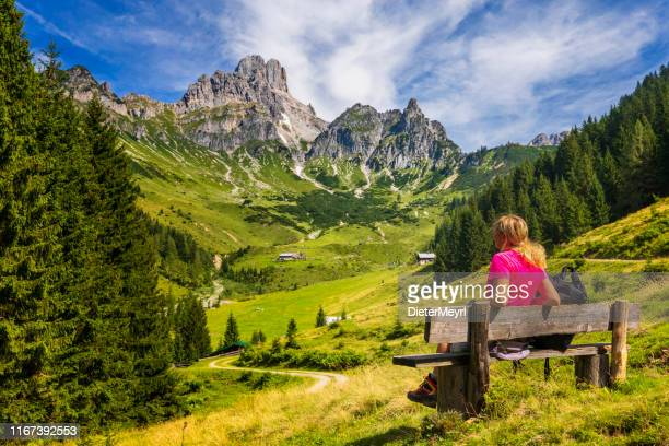young woman sitting on bench and enjoys view on big bischofsmütze, dachstein mountains, alps - salzburger land stock pictures, royalty-free photos & images