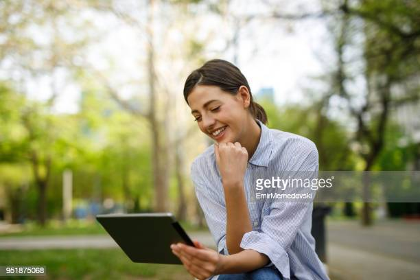 young woman sitting on bench and using digital tablet - emir memedovski stock pictures, royalty-free photos & images