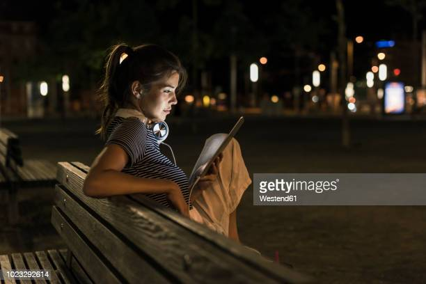 young woman sitting on bench at night using tablet - portability stock pictures, royalty-free photos & images