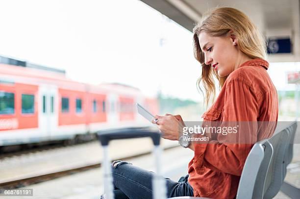 young woman sitting on bench at platform using tablet - bahnreisender stock-fotos und bilder