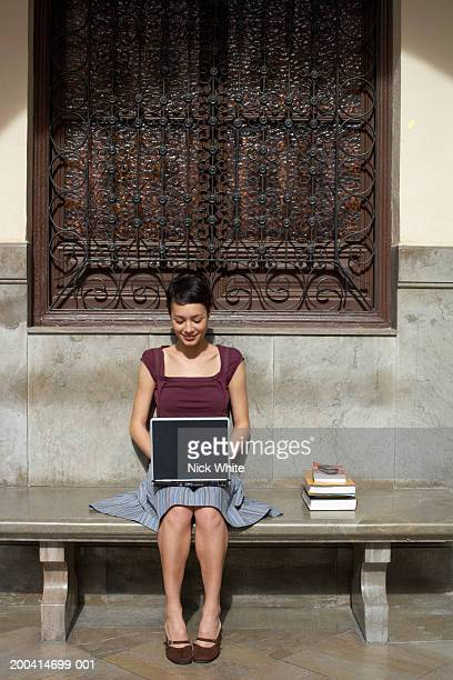 Young woman sitting on bench by books using laptop, smiling