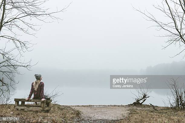 Young woman sitting on bench by misty lake