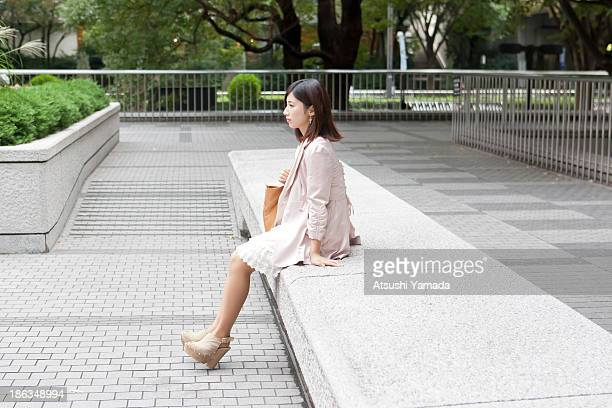 Young woman sitting on bench in city location