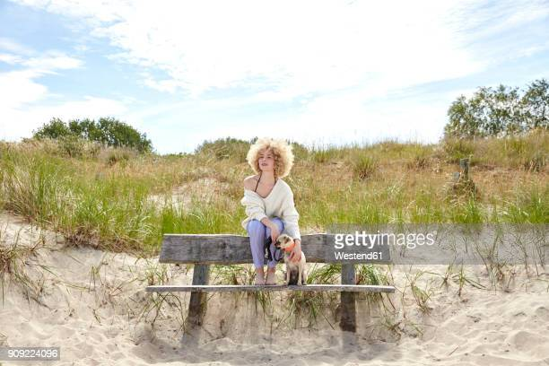 Young woman sitting on bench in the dunes with her dog looking at distance