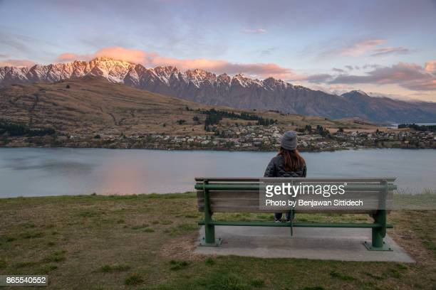 Young Woman sitting on bench looking at the Remarkable in Queenstown, New Zealand