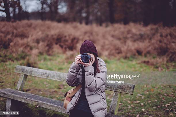 Young woman sitting on bench taking pictures