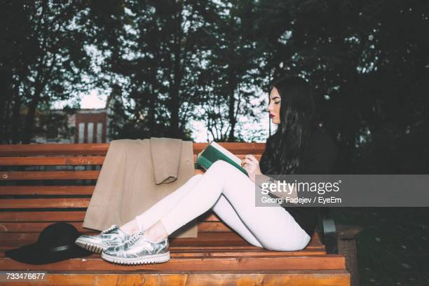 Young Woman Sitting On Bench With Book