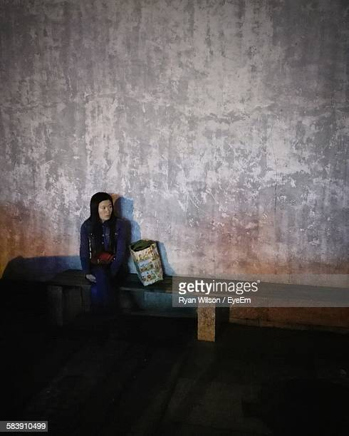 Young Woman Sitting On Bench With Shopping Bag Against Wall