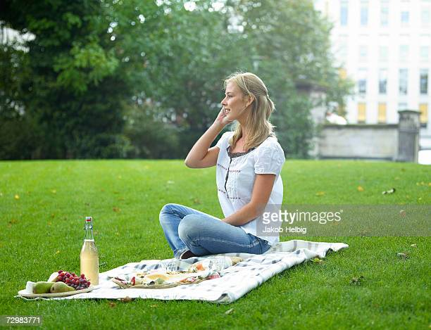 Young woman sitting on blanket with picnic in park, talking on phone
