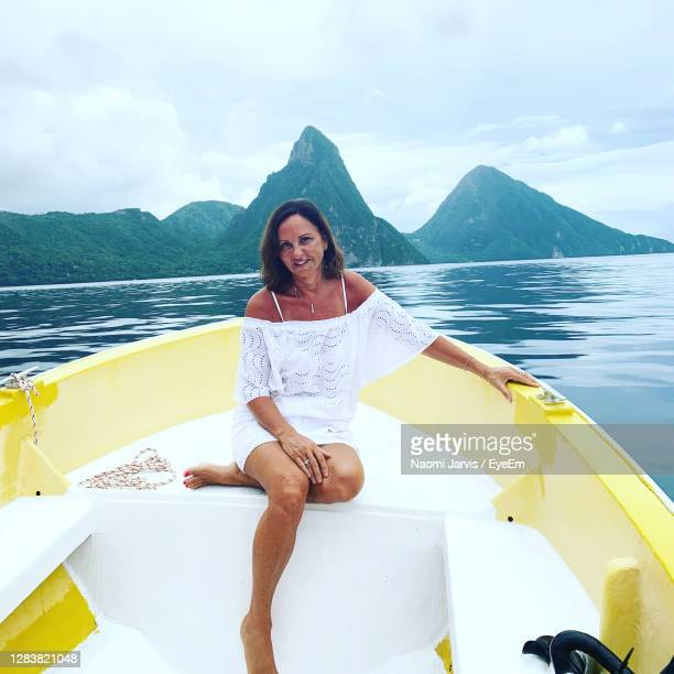 young woman sitting on boat against pitons - naomi jarvis stock pictures, royalty-free photos & images
