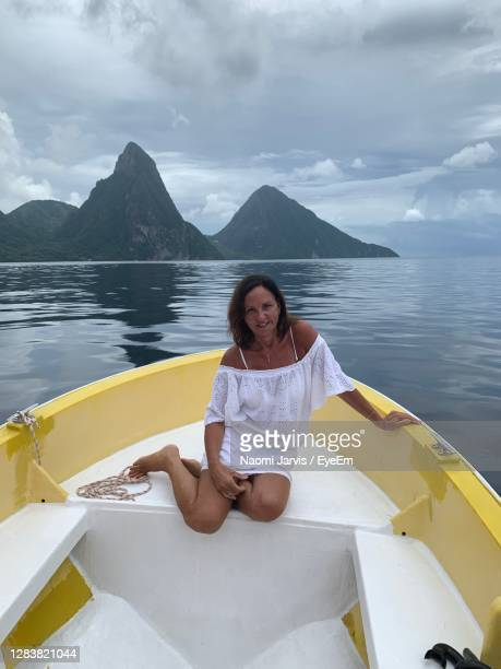 young woman sitting on boat against sky - naomi jarvis stock pictures, royalty-free photos & images