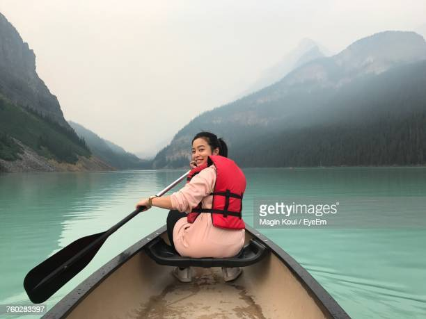 young woman sitting on boat in lake against mountains - lake louise stock pictures, royalty-free photos & images