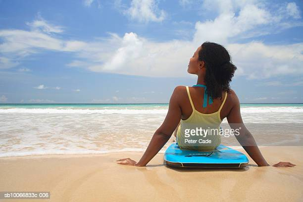 Young woman sitting on bodyboard at beach, rear view