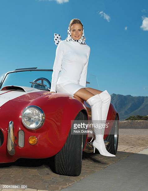 young woman sitting on bonnet of racing car on coast road, smiling - short skirts in cars stock photos and pictures