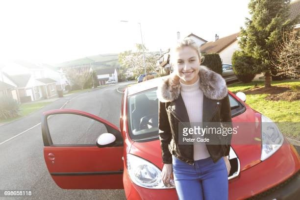 Young woman sitting on bonnet of red car