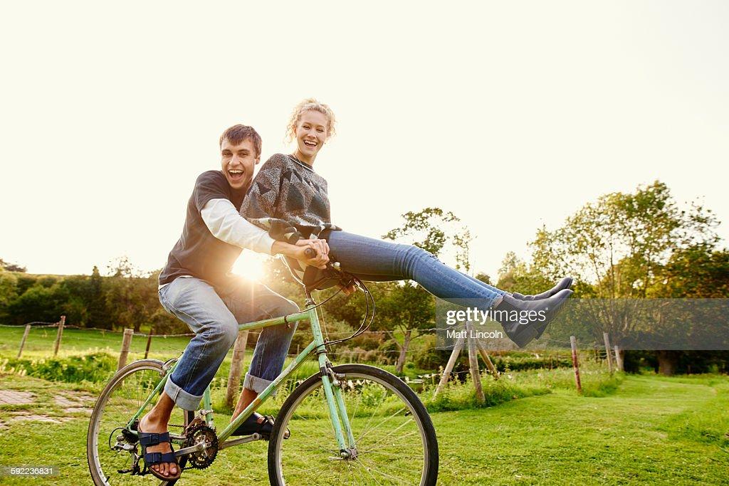 Young woman sitting on boyfriends bicycle handlebars : Stock Photo
