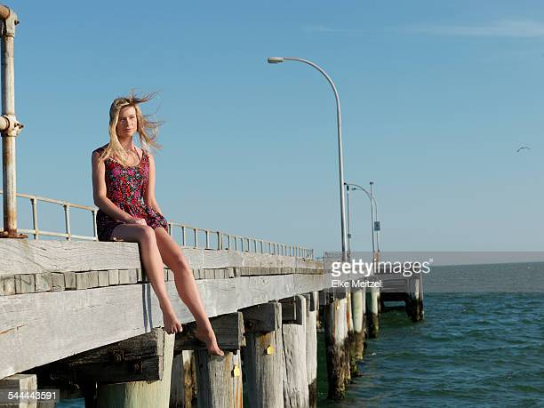 Young woman sitting on breezy pier, Altona, Melbourne, Victoria, Australia