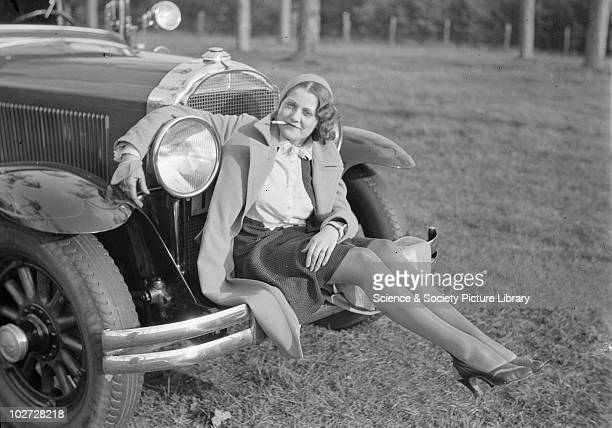 Young woman sitting on bumper of car smoking a cigarette Photograph taken by Zoltan Glass c1930 Photograph taken for advertisement series in the...