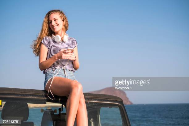 Young woman sitting on car on the beach