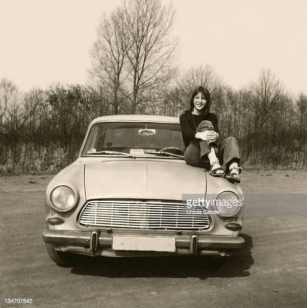 young woman sitting on car - archivmaterial fotos stock-fotos und bilder