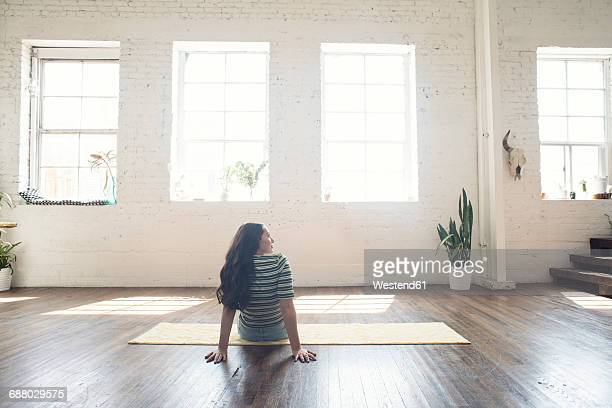 Young woman sitting on carpet in a loft