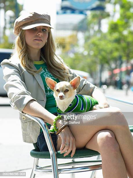 young woman sitting on chair, dog in lap - one animal stockfoto's en -beelden