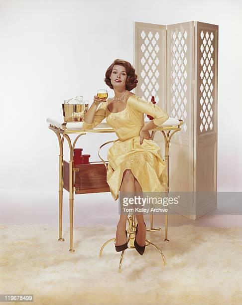 Jovem mulher sentada na cadeira segurando copo de cerveja com