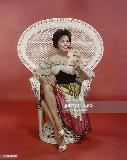 Young woman sitting on chair holding rose, smiling, portrait