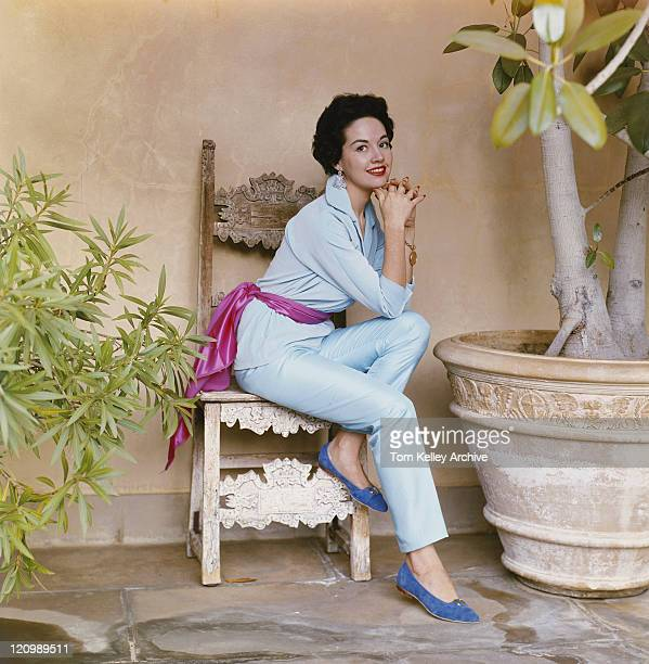 young woman sitting on chair, smiling, portrait - 1950 1959 stock pictures, royalty-free photos & images