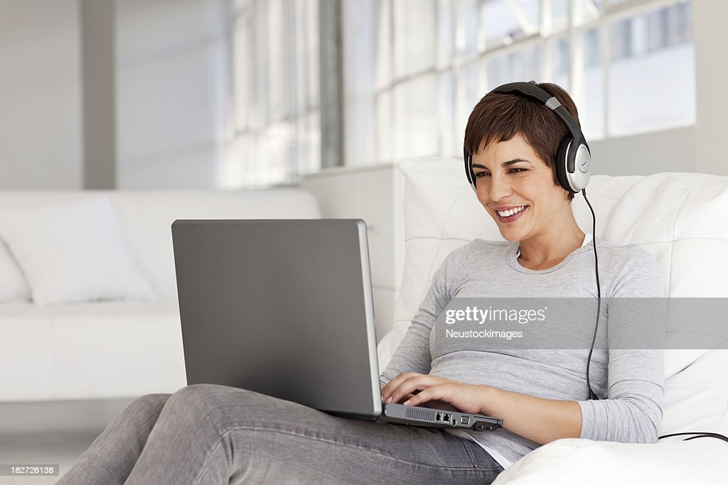 Young Woman Sitting on Chair Smiling Wearing Headphones : Stock Photo