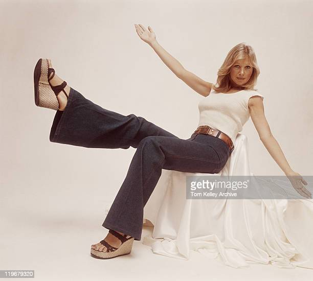 young woman sitting on chair with arms outstretched, portrait - 1970s stock photos and pictures