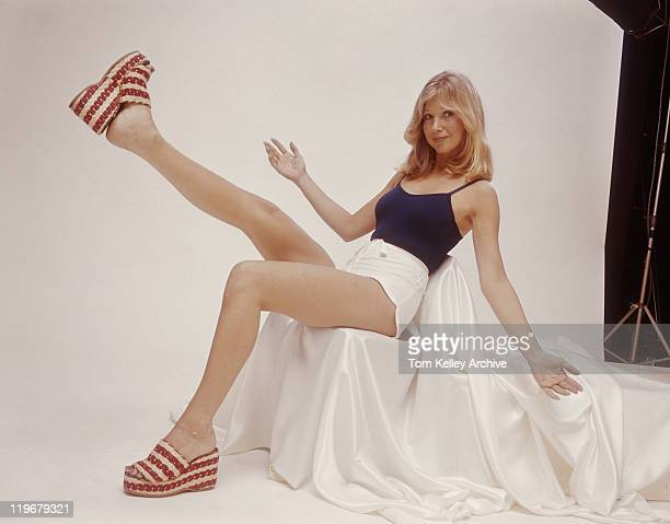young woman sitting on chair with arms outstretched, portrait - women in daisy dukes stock photos and pictures