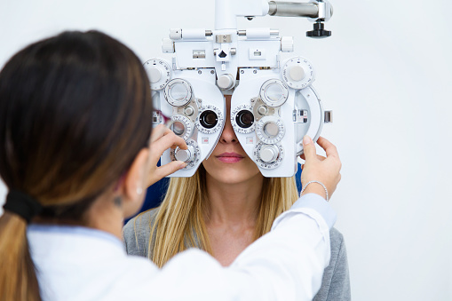 Young woman sitting on chair with beautiful optician standing while doing eye test in ophthalmology clinic. 1087284932