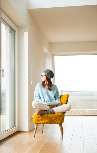 Young woman sitting on chair with digital tablet - gettyimageskorea