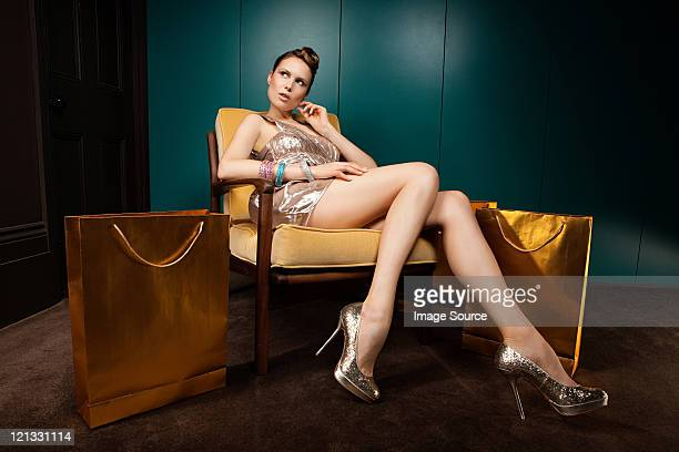 Junge Frau sitzend auf Stuhl mit Einkaufstaschen