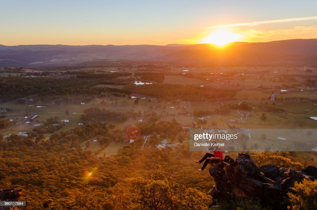 Young woman sitting on cliff taking photo at sunset : Stock-Foto