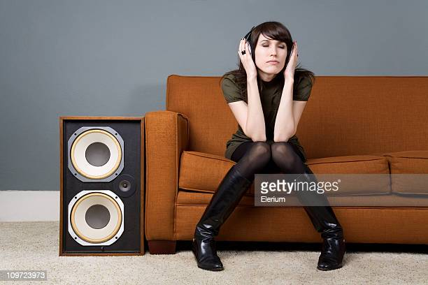Young Woman Sitting on Couch and Listening to Music