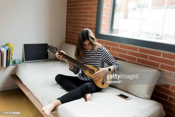 young woman sitting on couch at home playing guitar - 20 24 anos imagens e fotografias de stock