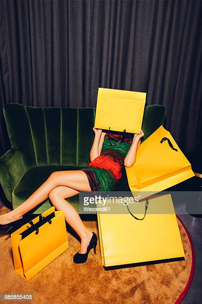 Young woman sitting on couch hiding her face behind a shopping bag