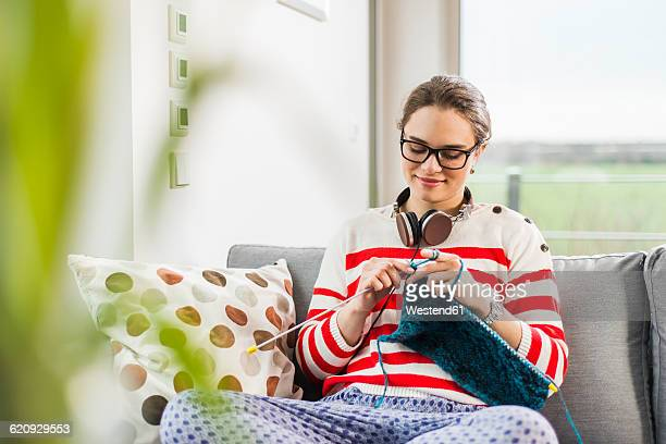 Young woman sitting on couch knitting