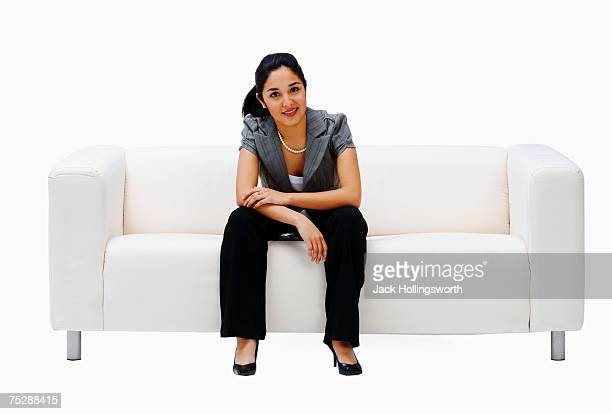 Young woman sitting on couch, smiling, portrait