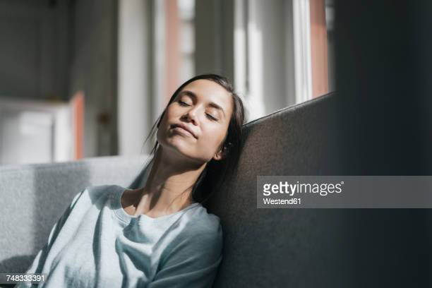 Young woman sitting on couch, taking a nap