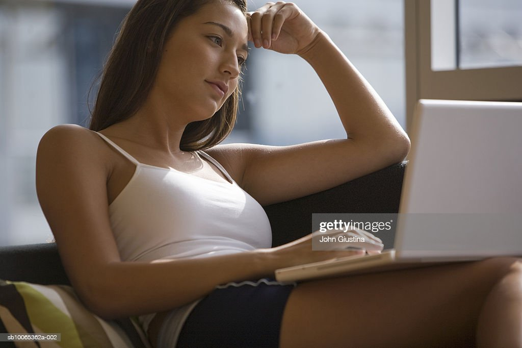 Young woman sitting on couch, using laptop : Foto stock