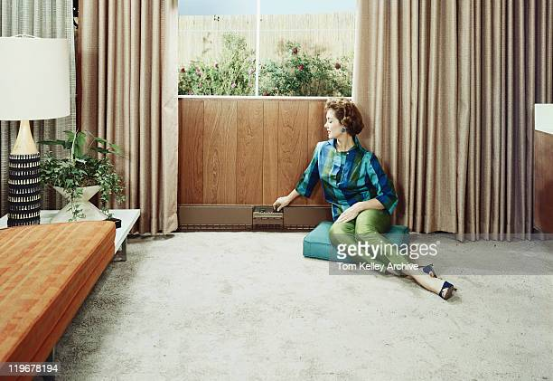 young woman sitting on cushion adjusting radiator's knob - 1950 1959 stock pictures, royalty-free photos & images