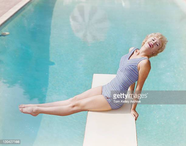Young woman sitting on diving board, smiling, portrait