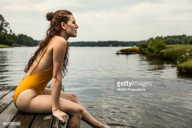 young woman sitting dock at lake